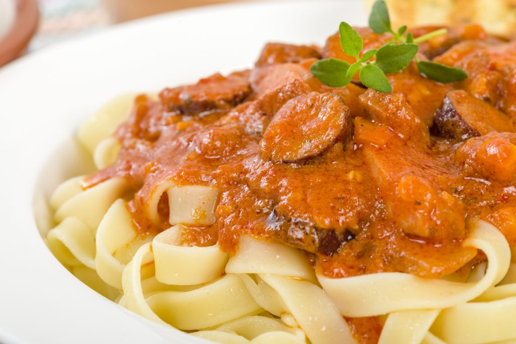 Szekely Gulyas - Hungarian goulash with beef and sour cream on top of pasta and served with a slice of crusty bread.