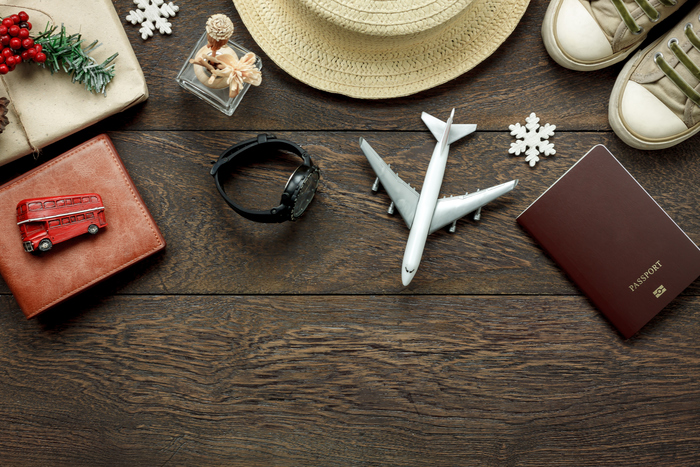 Above view shot of accessories fashion lifestyle to travel and Merry Christmas & Happy new year concept.Passport & clothes with many essential winter season background.Several objects on brown plank.